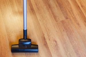 front view of vacuuming of laminate floor by vacuum cleaner at home